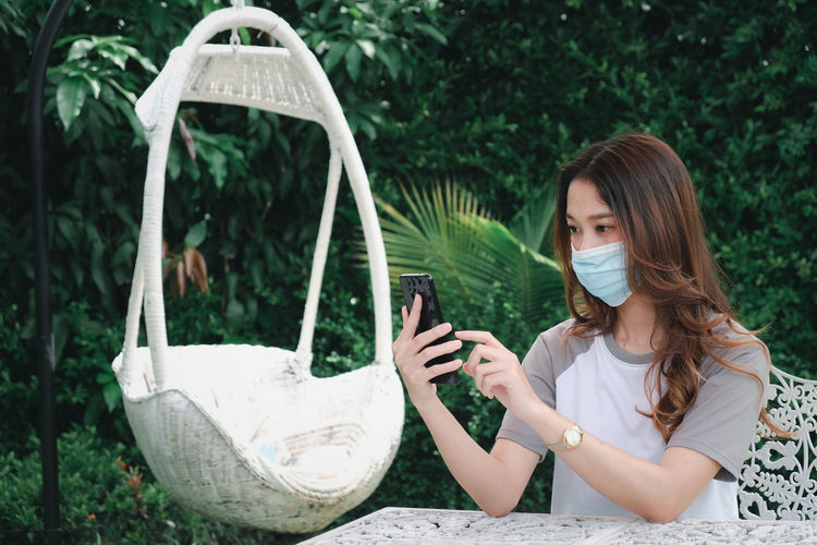 Young woman wearing mask using phone sitting outdoors