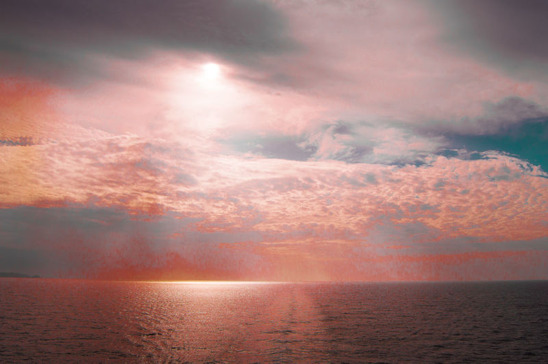 Beautiful magical dramatic sunset over the sea, pink background.