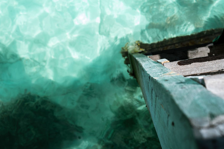 Wooden ladder on calm summer tropical sea with sparkling water in semporna, sabah.