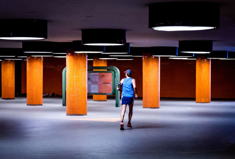Full Length Rear View Of Man Jogging In Illuminated Subway