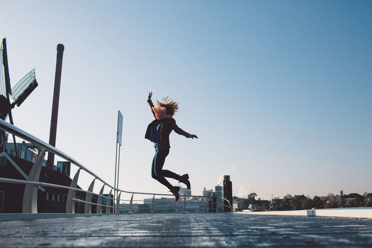 Full length of woman jumping against clear sky