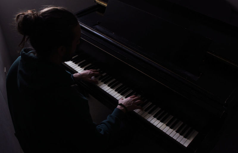 High angle view of man playing piano at home