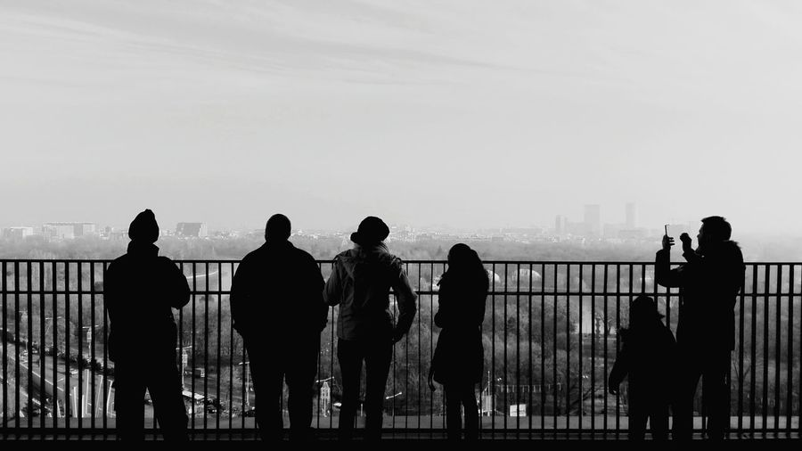 Rear view of silhouette people standing by railing against cityscape