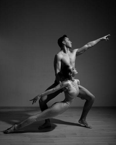 Full length of shirtless man dancing against white background