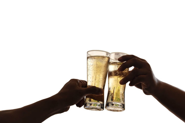 The hands of two men holding a glass of beer raised together to drink to celebrate the success, isolated on white background. Human Hand White Background Hand Drink Human Body Part Holding Studio Shot Refreshment Food And Drink Alcohol Glass Drinking Glass Copy Space Beer Beer - Alcohol Indoors  Household Equipment Celebratory Toast Celebration Close-up Finger Human Limb