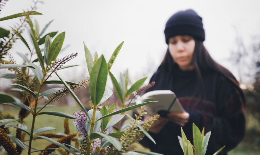 Young woman standing outdoor and reading a book.