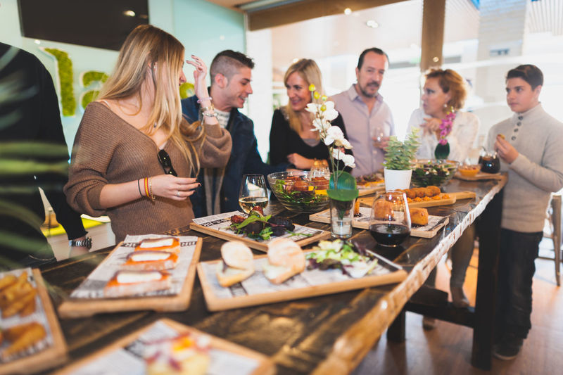 Happy friends by food at table in restaurant