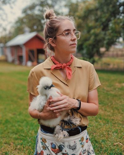 Young Woman Holding Silkie While Standing On Grassy Field