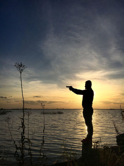A silhouette of a man standing in sunset in front of a lake aiming a gun