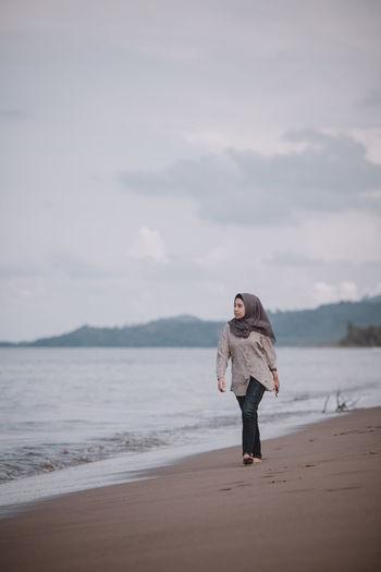 Full length of woman in hijab walking at beach against sky