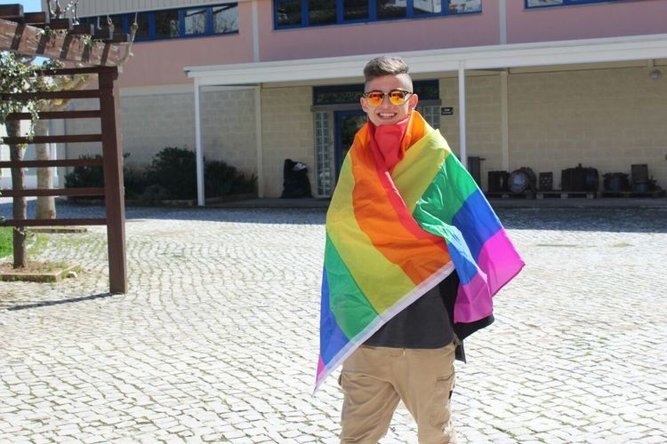 Happy Gay Man Wrapped In Rainbow Flag On Street