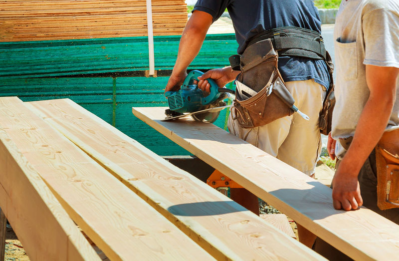 Midsection of carpenters working outdoors during sunny day