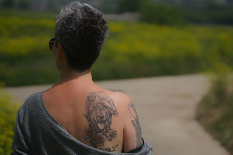 Rear view of woman with dog tattoo on back