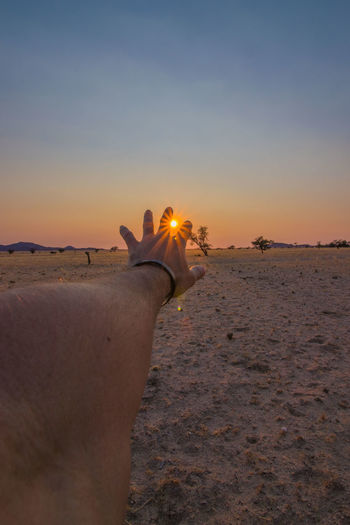 Man holding umbrella at beach during sunset