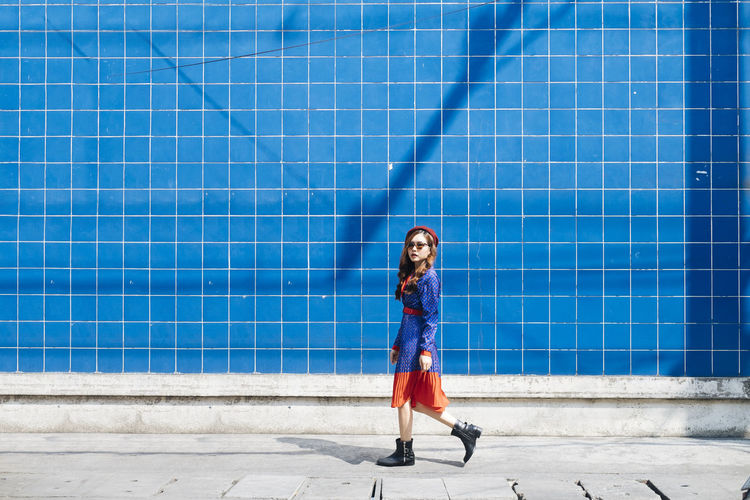 Portrait of smiling young woman walking by wall outdoors