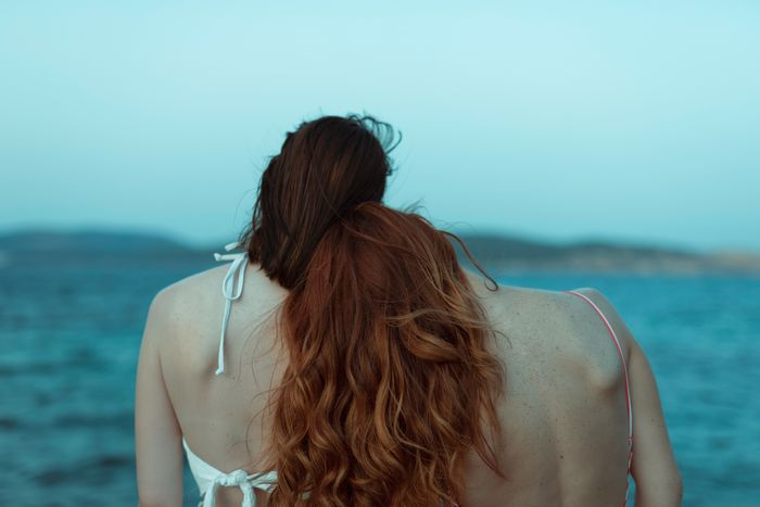 Rear view of lesbian couple at beach