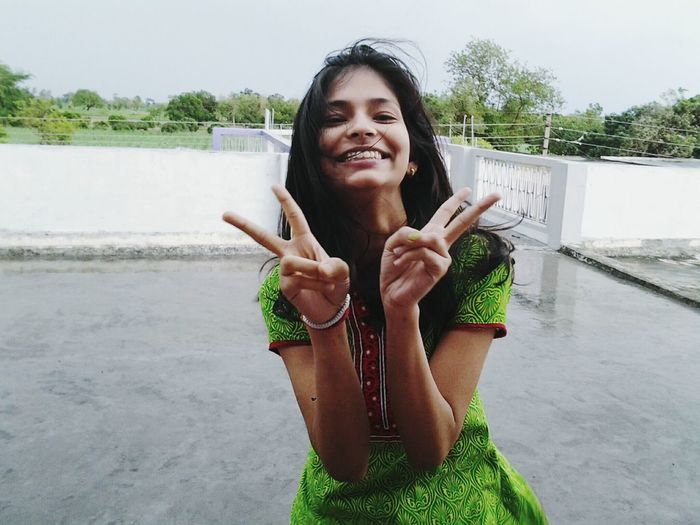 Portrait of cheerful young woman gesturing peace sign while standing on terrace
