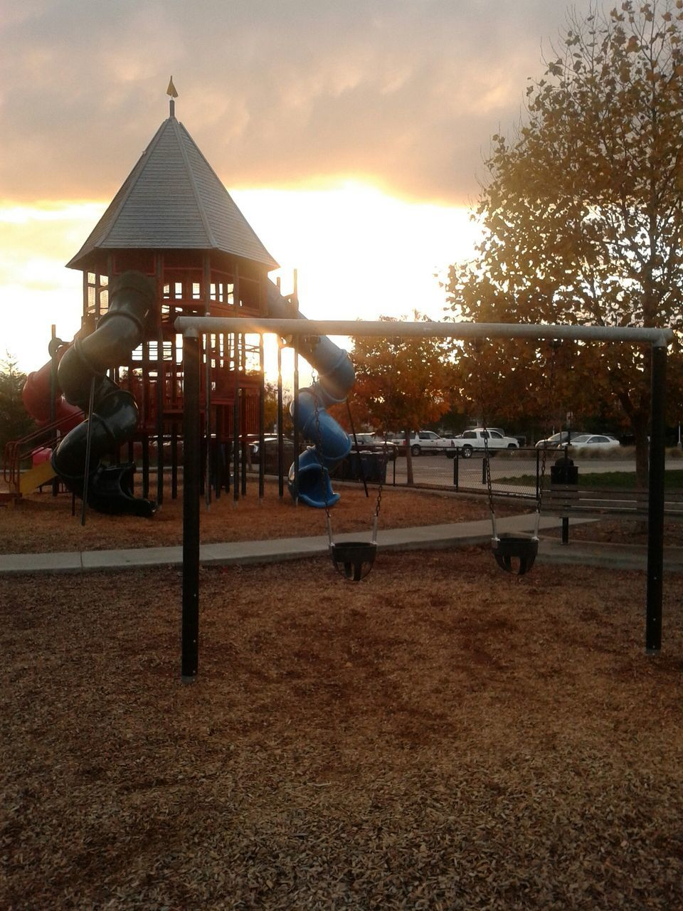sunset, playground, sky, silhouette, real people, tree, nature, leisure activity, childhood, full length, outdoors, outdoor play equipment, lifestyles, men, one person, beauty in nature, day, people