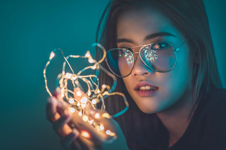Close-Up Portrait Of Young Woman Holding Illuminated String Light