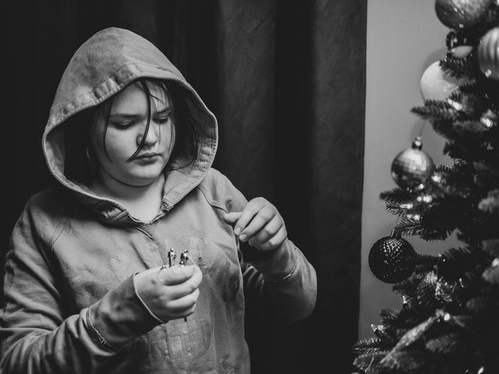 Girl wearing hooded shirt decorating christmas tree at home