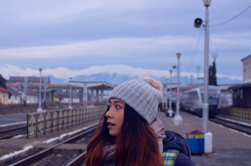 Close-Up Of Woman Looking Away At Railroad Station Platform Against Sky