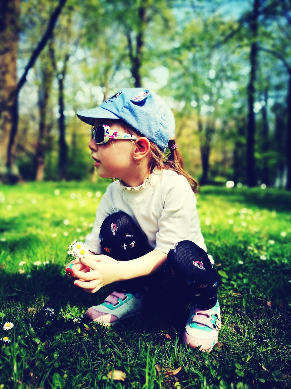 grass, childhood, one person, real people, nature, leisure activity, outdoors, cute, elementary age, tree, day, park - man made space, holding, sitting, lifestyles, girls, one animal, boys, playing, forest, animal themes, happiness, mammal, people