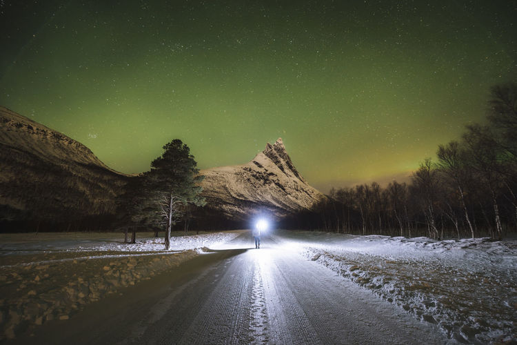 Late nights up north. Check out my prints at https://simonmigaj.com/shop/ and visit my IG http://www.instagram.com/simonmigaj for more inspirational photography from around the world. Road Transportation Sky Snow Direction Winter Night The Way Forward Scenics - Nature Nature Cold Temperature Beauty In Nature Mountain Star - Space Astronomy Outdoors Tranquility Aurora Aurora Borealis Northern Lights Norway Norge Travel Travel Photography Stars