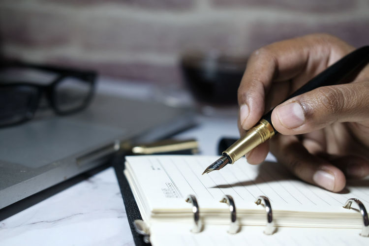 Close up of man hand writing on notepad