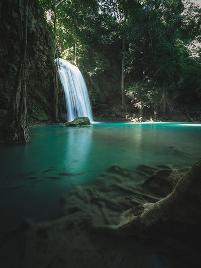 Scenic waterfall with turquoise pond and sunbeam in forest. erawan falls, kanchanaburi, thailand.