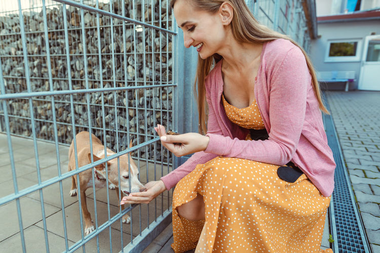 Woman feeding dog while crouching by fence