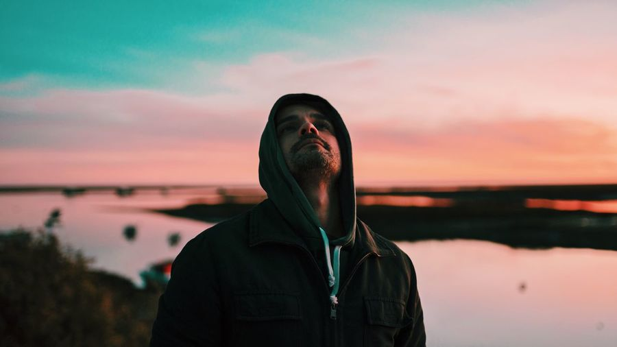 Portrait of man standing by lake against sky during sunset