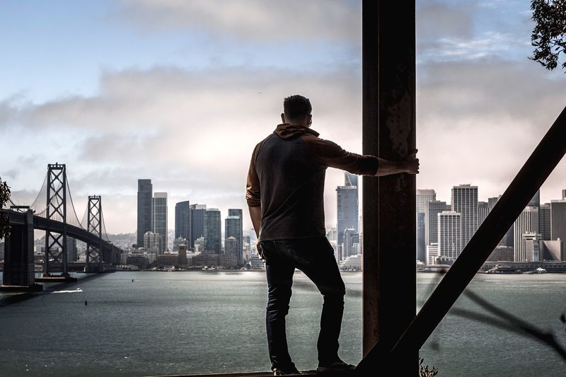 Rear view of man looking at buildings against sky