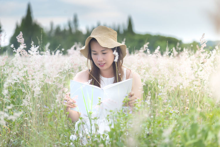 reading Beautiful Woman Clothing Contemplation Day Field Flower Front View Grass Hat Holding Land Leisure Activity Lifestyles Nature One Person Outdoors Plant Real People Selective Focus Sun Hat Women Young Adult Young Women