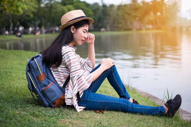 Cry Stress Unhappy Adult Beautiful Woman Exhausted Fatigue  Frustrated Grass Hat Lifestyles Nature One Person Outdoors Problem Relaxation Sadness Sitting Strain Tension Tired Weep Woeful Young Adult Young Women