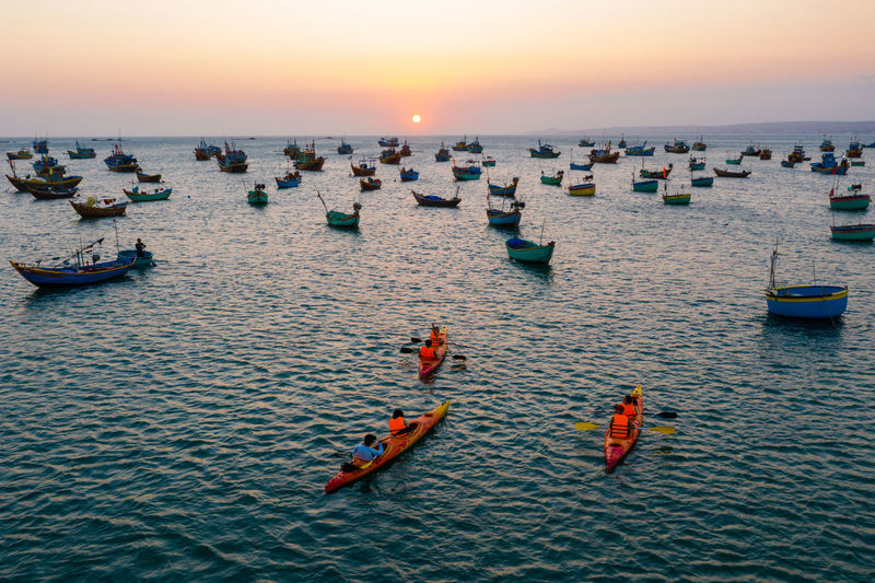 Boats in sea against sky during sunset