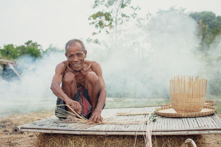 Shirtless senior man making straw basket