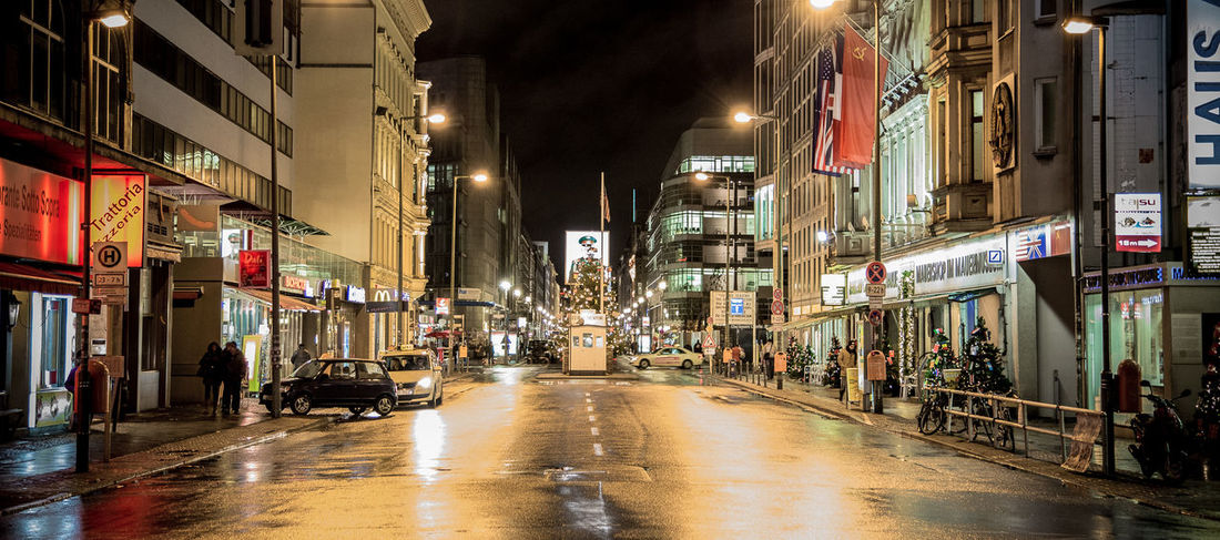 City EyeEmNewHere. Night Lights Night Photography Nightphotography The Week On EyeEm Architecture Building Exterior Built Structure Checkpointcharlie City Illuminated Night Night View No People Outdoors Sky Street Street Photography Streetart Streetphotography Wet Discover Berlin #FREIHEITBERLIN