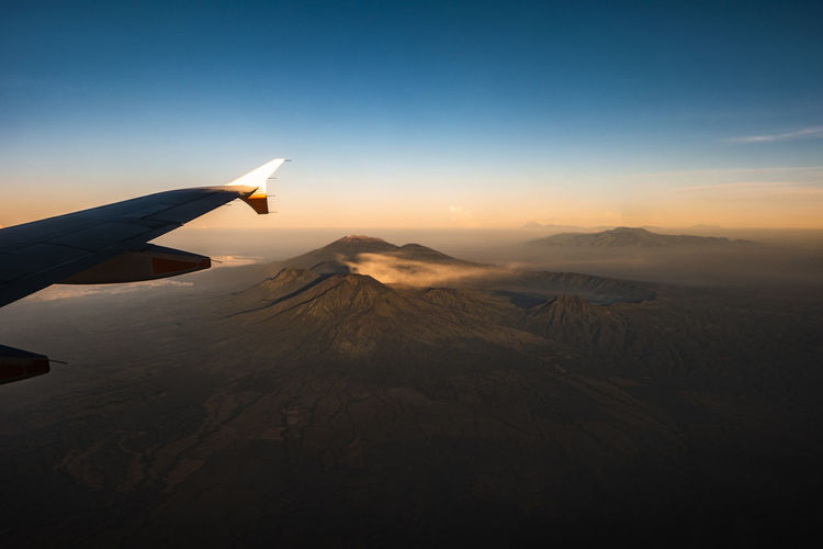 Airplane flying over snowcapped mountains against sky during sunset