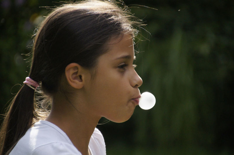Close-up of girl blowing bubble gum outdoors