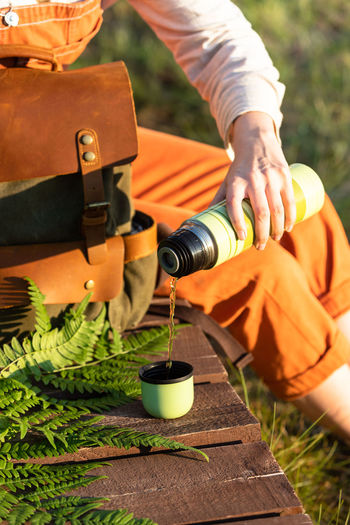 Midsection of woman pouring water in cup while sitting outdoors