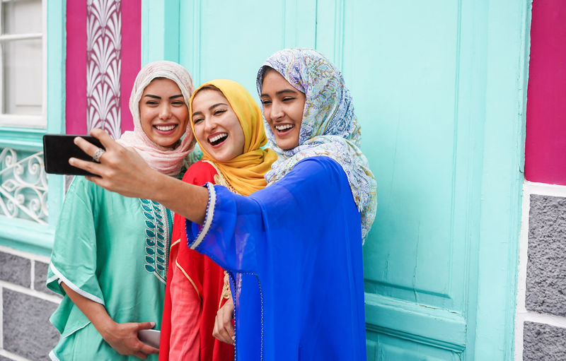 Arabian women friends taking selfie photo with smartphone outdoor Smiling Happiness Women Portrait Emotion Young Women Young Adult Friendship Togetherness Group Of People Arabic Arabian Muslim Hijab Millenials