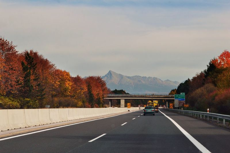Outdoors Landscape Tree Mountain Road Autumn Road Sign Highway Driving Asphalt Road Marking Sky Two Lane Highway Empty Road Dividing Line Mountain Road Diminishing Perspective Treelined vanishing point Country Road Car Point Of View
