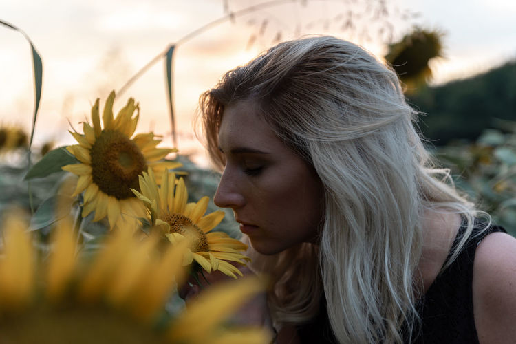 Close-up of young woman smelling sunflower at farm