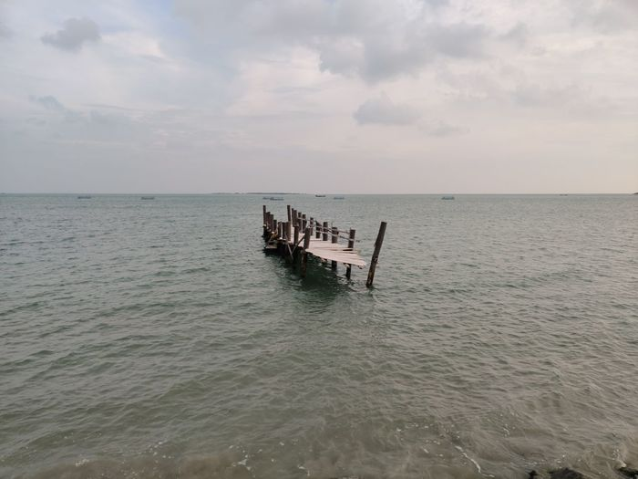 Scenic view of wooden posts in sea against sky