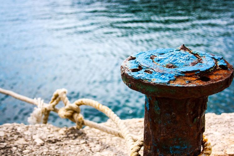 Close-up of rusty metallic bollard by sea