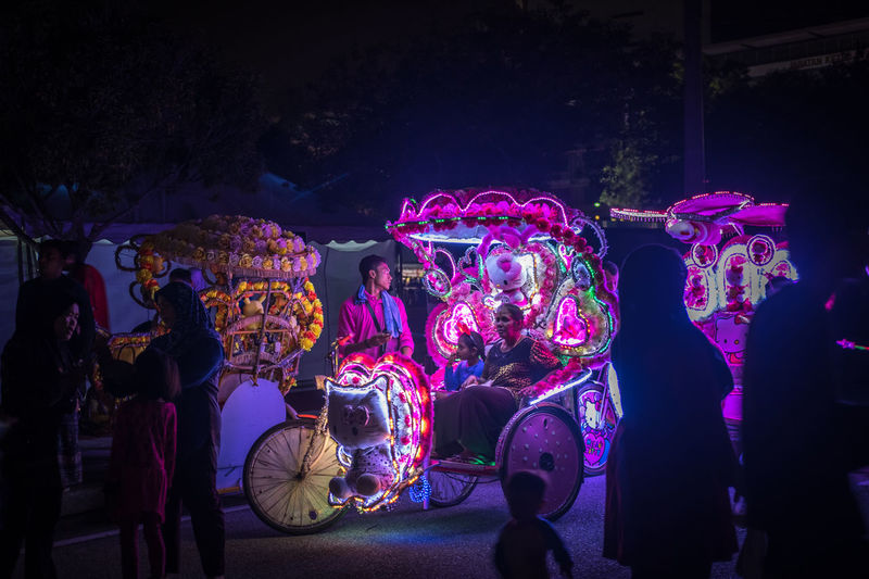 A woman and her daughter on an illuminated cycle rickshaw/trishaw at the Festival Light And Motion Putrajaya (LAMPU) 2017, Putrajaya, Malaysia Festival Season Light Light Festival Rickshaws Transportation Trishaw Bicycle Child Colorful Cycle Rickshaw Festival Festival Of Lights Illuminated Mixed Age Range Multi Colored Night People Real People Rickshaw Rickshaw Ride Togetherness Women