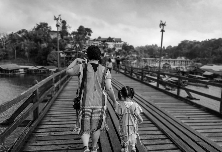 Rear view of mother and daughter walking on footbridge