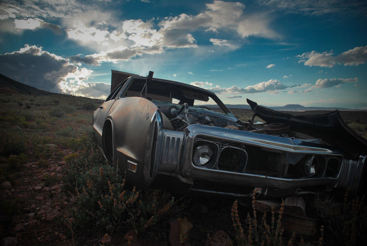 Abandoned car on landscape against sky