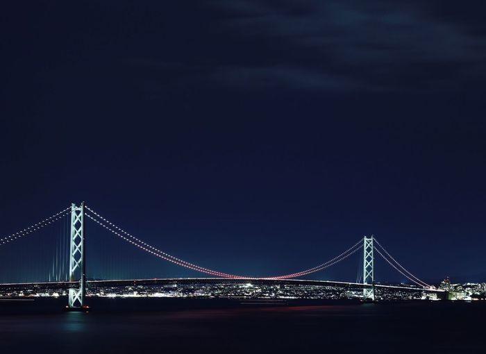 Illuminated akashi strait bridge over sea against clear sky at night