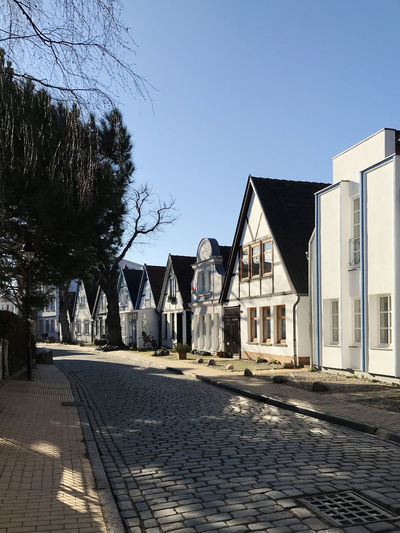 cobblestone street in warnemünde Architecture Built Structure Building Exterior Sky Nature Clear Sky Tree Building Plant Sunlight Cobblestone Day No People Footpath Street Shadow Blue Outdoors House City Paving Stone Row House Warnemünde